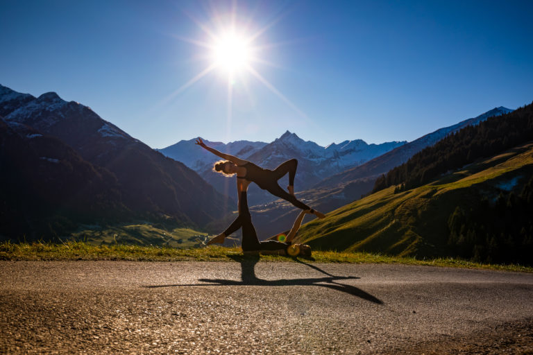 Teachers Gabe & Loli in an AcroYoga pose in the Swiss Mountains.